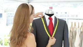 Pretty fashion designer measuring suit lapels on mannequin stock video footage