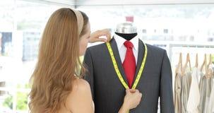 Pretty fashion designer measuring suit lapels on mannequin stock footage