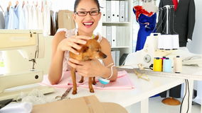 Pretty fashion designer petting her chihuahua stock footage