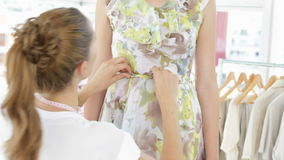 Pretty fashion designer tying belt of floral dress on a model Stock Image