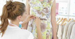 Pretty fashion designer tying belt of floral dress on a model stock footage