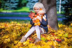 Pretty Fashion girl sitting under a maple tree. Pretty Fashion girl sits under a maple tree with doll and red leaf on sunny autumn day Royalty Free Stock Photo