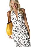 Pretty Fashion Model. With blonde hair walking in halter dress carrying a yellow bag royalty free stock image