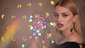 Pretty fashion model plays with electric garland in yellow lights bokeh background, slow motion. Pretty fashion model plays with colorful electric garland in stock video footage