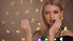 Pretty fashion model plays with electric garland in yellow lights bokeh background, slow motion. Pretty fashion model plays with colorful electric garland in stock video
