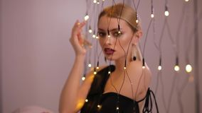 Pretty fashion model plays with electric garland, slow motion. Pretty fashion model plays with yellow electric garland, slow motion stock footage