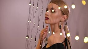 Pretty fashion model plays with electric garland, slow motion. Pretty fashion model plays with yellow electric garland, slow motion stock video footage