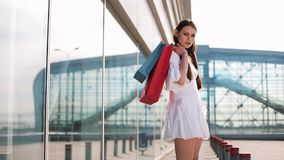 Pretty fashion model in white dress poses with shopping bags before a modern glass building.  stock video footage