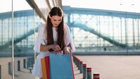 Pretty fashion model in white dress poses with shopping bags before a modern glass building
