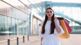 Pretty fashion model in white dress poses with shopping bags before a modern glass building.  stock video