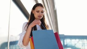 Pretty fashion model in white dress poses with shopping bags before a modern glass building stock video