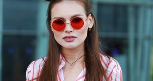 Pretty fashion in red sunglasses poses to the camera with before a modern glass building. A young transgender looking stock footage