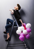 Pretty fashion retro teen girl laughing on ladder Royalty Free Stock Image