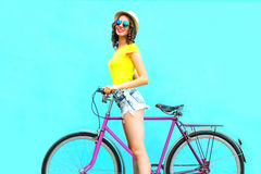 Pretty fashion smiling woman with retro pink bicycle over colorful blue Royalty Free Stock Photography