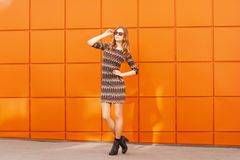 Pretty fashion woman in dress and sunglasses.Background of a bri Stock Photo