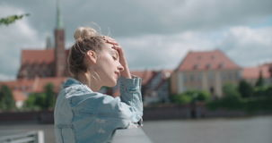 Pretty fashion woman relaxing in a city park in Europe. Happy stylish girl wearing denim jacket enjoying time during sunny day stock video