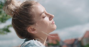 Pretty fashion woman relaxing in a city park in Europe. Happy stylish girl wearing denim jacket enjoying time during sunny day stock video footage