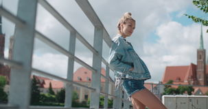 Pretty fashion woman relaxing in a city park in Europe. Happy stylish girl wearing denim jacket enjoying time during sunny day stock footage