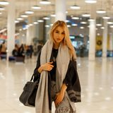 Pretty fashionable attractive woman in a gray stylish coat with a trendy vintage scarf with a leather black handbag stock photo