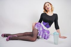 Pretty fashionable blonde girl wearing black jumpsuit with mesh pantyhose and purple corset on white background. Isolated stock photos