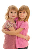 Pretty fashionable little girls. Two little fashionable girls are standing together and hugging each other; isolated on the white background Stock Images