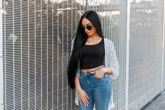 Pretty fashionable young hipster woman with beautiful long hair in trendy youth clothes is standing near a metal wall in the city royalty free stock image