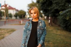 Pretty fashionable young woman blonde in blue vintage denim jacket with trendy leather handbag in dress posing on the street. Near the trees on a summer day stock photo