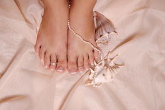 Pretty feet. A pair of pedicured woman's feet with a pearl necklace and seashells Stock Images