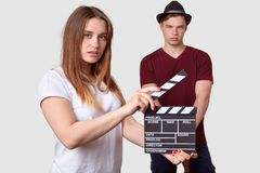Pretty femake in white t shirt holds clapper board, shoots scene, serious stylish man stands in foreground, wears stylish headgear. Pretty femake in white t royalty free stock photography