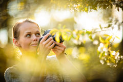 Pretty female amateur photographer taking photos outdoors. Doing what she loves to do royalty free stock image