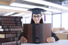 Pretty female bachelor read textbooks Stock Photo