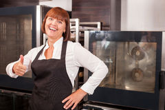 Pretty female baker is expressing positive Royalty Free Stock Image