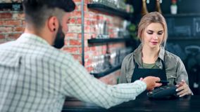 Pretty female barista serving coffee cup for male customer enjoying positive emotion. Medium shot. Trendy man buying morning hot beverage paying using mobile stock video footage