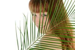Pretty female behind palm leaf Royalty Free Stock Photos