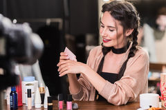 Pretty female blogger using cosmetic product Royalty Free Stock Images