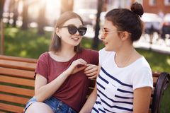 Pretty female with bobbed hairstyle, wears trendy shades, has pleasant talk with her best friend, shares impressions after travell. Ing abroad, discuss something stock photos