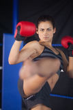 Pretty female boxer performing an air kick in the ring Royalty Free Stock Photo