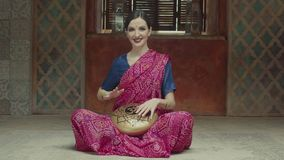 Pretty female calmly drumming hank drum with hands. Affectionate woman playing ethnic indian music using tank drum with om sign. Pacified female in hindu dress stock video footage