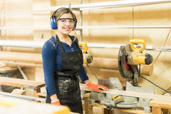 Pretty female carpenter using power tools. Portrait of a beautiful Latin female carpenter using a circular saw and some other power tools at work Stock Image