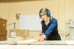 Pretty female carpenter using a table saw Royalty Free Stock Photos