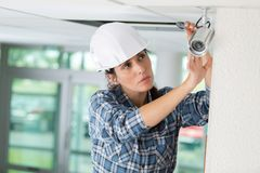 Pretty Female Cctv Installing Security Camera Royalty Free Stock Photos