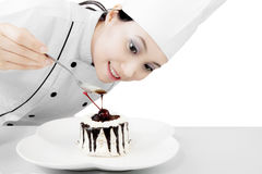 Pretty female chef with dessert. Image of pretty female chef finishing dessert while putting chocolate on a sweet cake royalty free stock photos