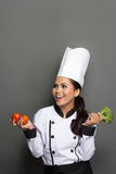 Pretty female chef playing with broccoli Stock Image