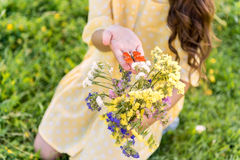Pretty female child holding little moth near flowers royalty free stock photography