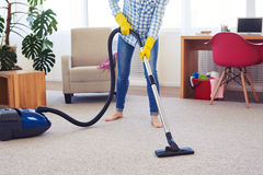 Pretty female cleaning with vacuum cleaner carpet Royalty Free Stock Image