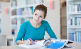 Pretty female college student in a library. (shallow DOF; color toned image Royalty Free Stock Images
