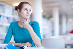 Pretty female college student in a library. (shallow DOF; color toned image Royalty Free Stock Photos