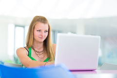 Pretty female college student  in the library. In the library - pretty female student with laptop and books working in a high school library (color toned image Royalty Free Stock Photography