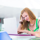 Pretty female college student in the library. In the library - pretty female student with laptop and books working in a high school library (color toned image Royalty Free Stock Photos