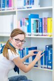 Pretty, female college student in a library royalty free stock images